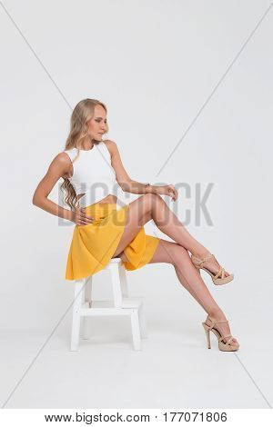Girl with perfect body in yellow skirt on white background.