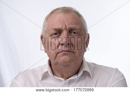 Close up portrait image of a mature man looking annoyed. Taken on a white background