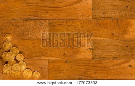 Wooden background of table with gold eagle coins in the corner to make a design for website with copy space