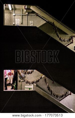 Hong Kong China - 16 November 2009: Strings of fish drying in a stairway at the wet market in Mongkok District at night