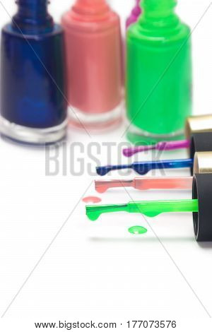 Row of brushes with colored nail polish and bottles on white background. Shallow depth of field