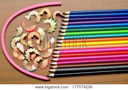 A set of eighteen colored pencils laid out in a straight row close scattered shavings from these pencils is surrounded by a flexible pencil.