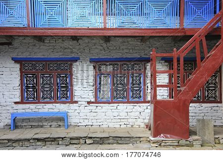 Grunge gray bricks wall with red windows and white curved steel it is a side view of traditional Nepali house in countryside.
