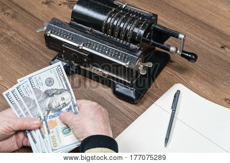 Hands of person counting the dollars at the table. Horizontal indoors shot
