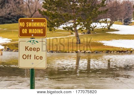 Keep Off Ice & No Swimming Or Wading Signs On Winter Pond