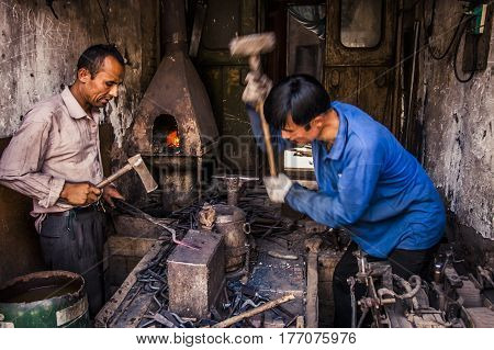 Kashgar China - 2 July 2009: Blacksmiths working on a piece of metal inside the old town district of the city