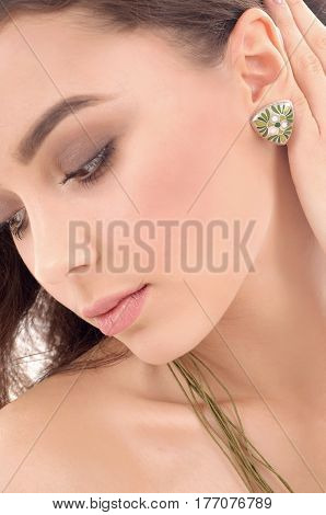 fashion closeup portrait of beautiful european model with long brown hair fresh skin wearing accessories and jewelry isolated over white background
