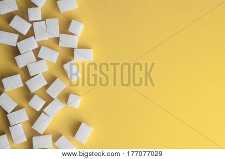 White sugar on yellow background. Cubes sugar with copy space. Top view or flat lay