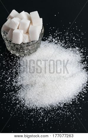 white granulated sugar in bowl and refined sugar on black background