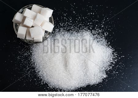 white sugar on black background. white granulated sugar and refined sugar on black table surface.