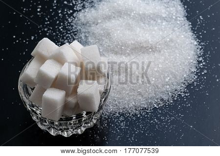 white granulated sugar and refined sugar on black table surface.
