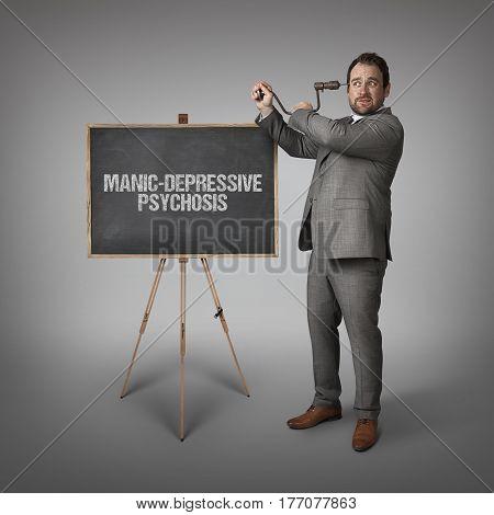 Manic Depressive psychosssive psychosis text on blackboard with businessman drilling his head