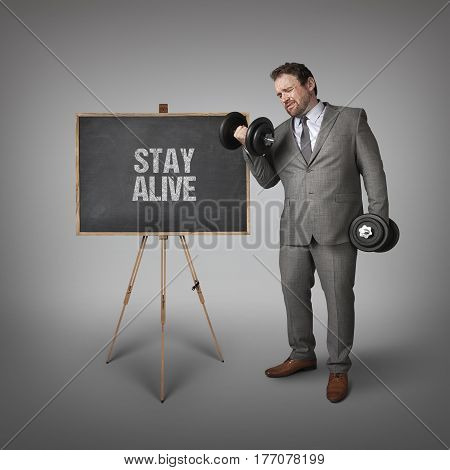 Stay alive text on blackboard with businessman holding weights