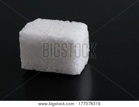 Single Cube of Sugar Isolated on Black Background.