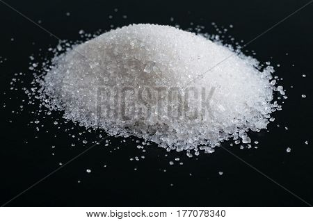 Heap of granulated sugar isolated on black