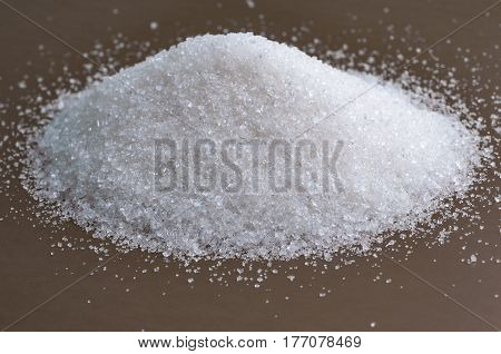 Heap of white sugar on a gray background