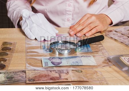 Collectible Coins And Banknotes In The Cells And Magnifying Glass