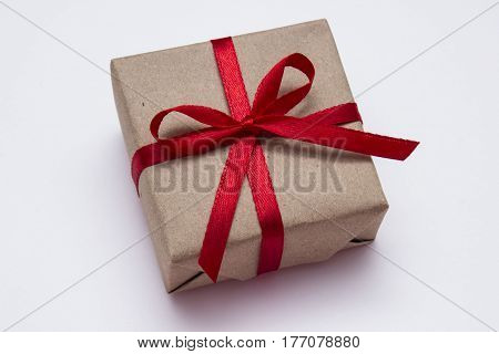 Small gift box with red ribbon on white background