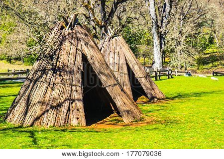 Two Historic American Indian Tepees In Field