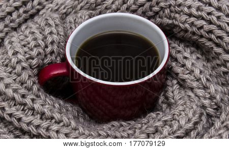 A cup of coffee wrapped in a warm scarf with a large viscous