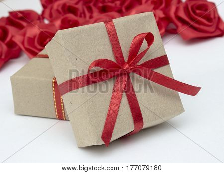 Gift boxes with red satin ribbons and red satin roses in the background