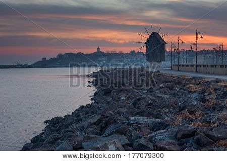 Old windmill in the ancient town of Nesebar in Bulgaria.The entrance to the old town. UNESCO world heritage site. Road, night lights. Car light trails. Long exposure.