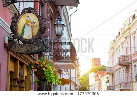 Vilnius Lithuania - August 7 2012: Forged signboard with image of woman with tea tray over entrance to cafe. Baltic architecture of central street of old city view of mountain and Gedimin's Tower