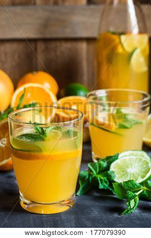 Healthy citrus lemonade from oranges fresh mint lime in glasses and bottle on dark stone kitchen table by window sunlight
