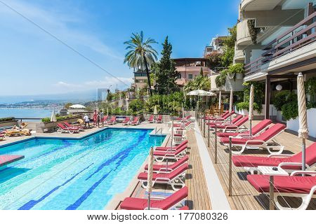 TAORMINA ITALY - MAY 17 2016: Swimming pool of a four star hotel in Taormina with a beautiful view at the Sicilian coast