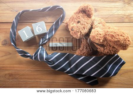 vintage wood calendar for june 16 with teddy bear and necktie Happy Father's Day inscription background concept.