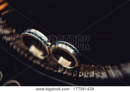 Luxury wedding rings with sapphires on a vintage typewriter