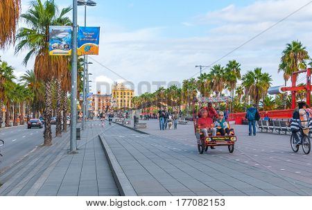 Barcelona, Spain, Nov 3rd, 2013: Tourism economy in Europe, people ride in a rickshaw, on bicycles & walking, taking advantage of warm weather.  Young people walk their dog along the city's palm tree lined roads.