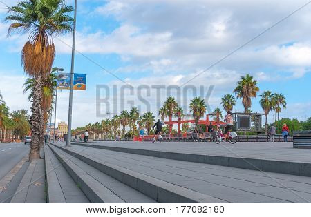 Barcelona, Spain, Nov 3rd, 2013: Tourism economy - Urban outdoors, people take advantage of warm weather.  Walking, running, bicycling & exercising.