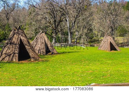 Three American Indian Tepees In Large Meadow