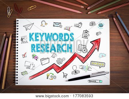 Keywords Research Business Concept. Notebooks, pen and colored pencils on a wooden table.