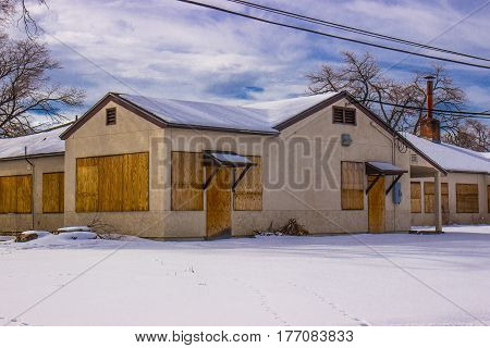 Old Boarded Up Commercial Building With Snow On Ground
