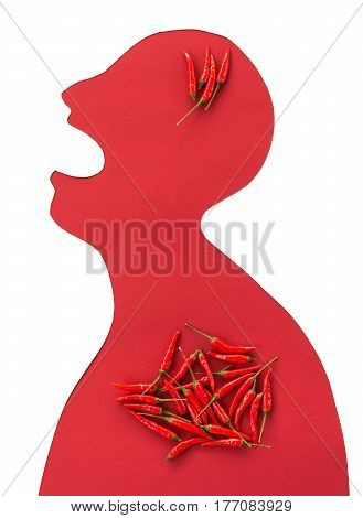 the contour of the person cut from red paper on a white background with an open mouth and hot red peppers lying inside him. concept of heartburn, spicy food, strong ilness. top view, flat lay.