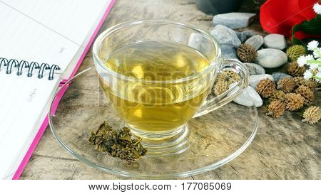 Hot tea in the morning. A Cup of tea on the wood desk with flowers background