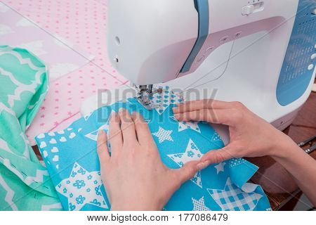 Woman's hands with dress at sewing machine close up