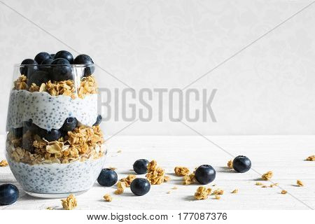blueberry yogurt parfait with granola oats and chia seeds in a glass on white wooden table. healthy breakfast. close up