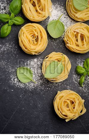 Raw tagliatelle pasta on the black concrete background, top view, copy space.