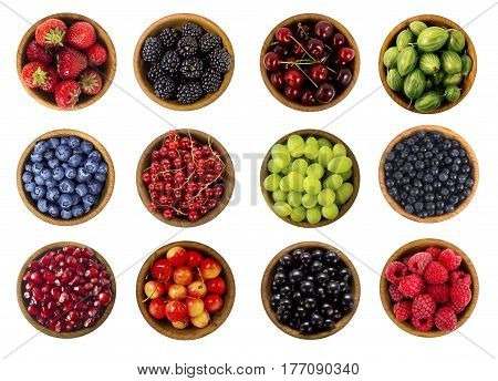 Collage of different fruits and berries isolated on white. Blueberries cherries blackberries grapes strawberries currants and pomegranate. Collection of fruits and berries in a wooden bowl. Top view.
