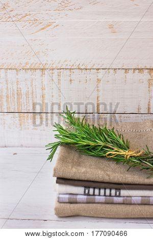 Pile of stacked folded kitchen towels on white plank wood background rosemary twig rustic minimalistic style kinfolk
