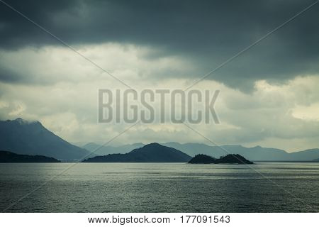 Seascape with moody sky and distant mountains