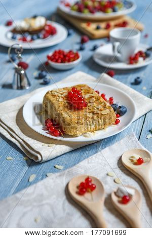 Sweet breakfast with pastry pie and berries - cowberry, red currant and bluberries. Beautiful food served at blue rustic wooden table, cake dessert at porcelain plate, vertical