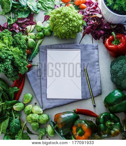 Fresh vegetables flatlay overhead frame. Open Notebook with vegetables.. Food layout. Diet. Dieting plan
