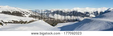 Panoramic view down snow covered valley in alpine mountain range with conifer pine trees and clouds
