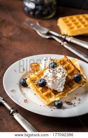 Belgian waffles on white plate on rustic background.