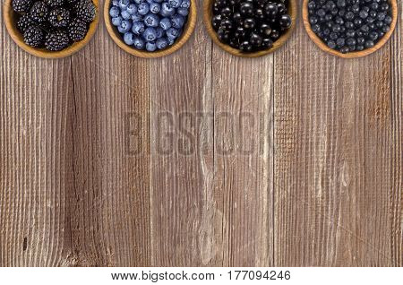 Black and blue berries. Blackberries blueberries currants and blueberries in a wooden bowls. Berries at border of image with copy space for text. Top view.