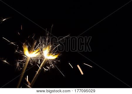 Two bright festive Christmas sparklers on black background with free space
